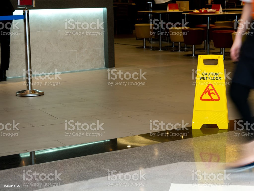 yellow plastic cone with sign showing warning of wet floor in...