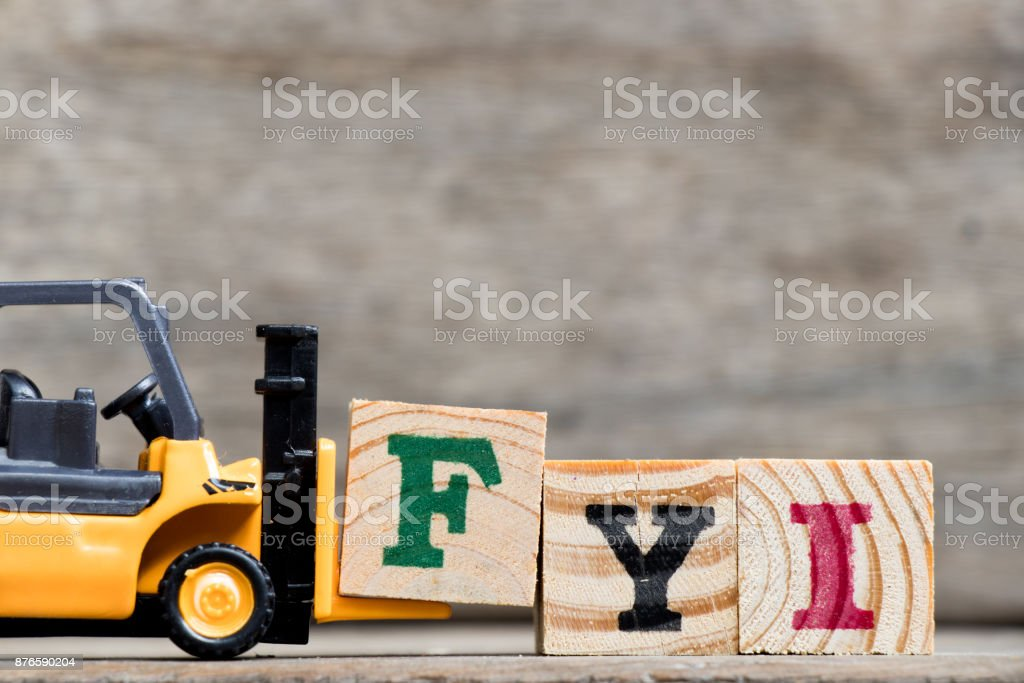 Yellow plastic forklift hold letter F to complete word FYI (Abbreviation of For your information) on wood background stock photo