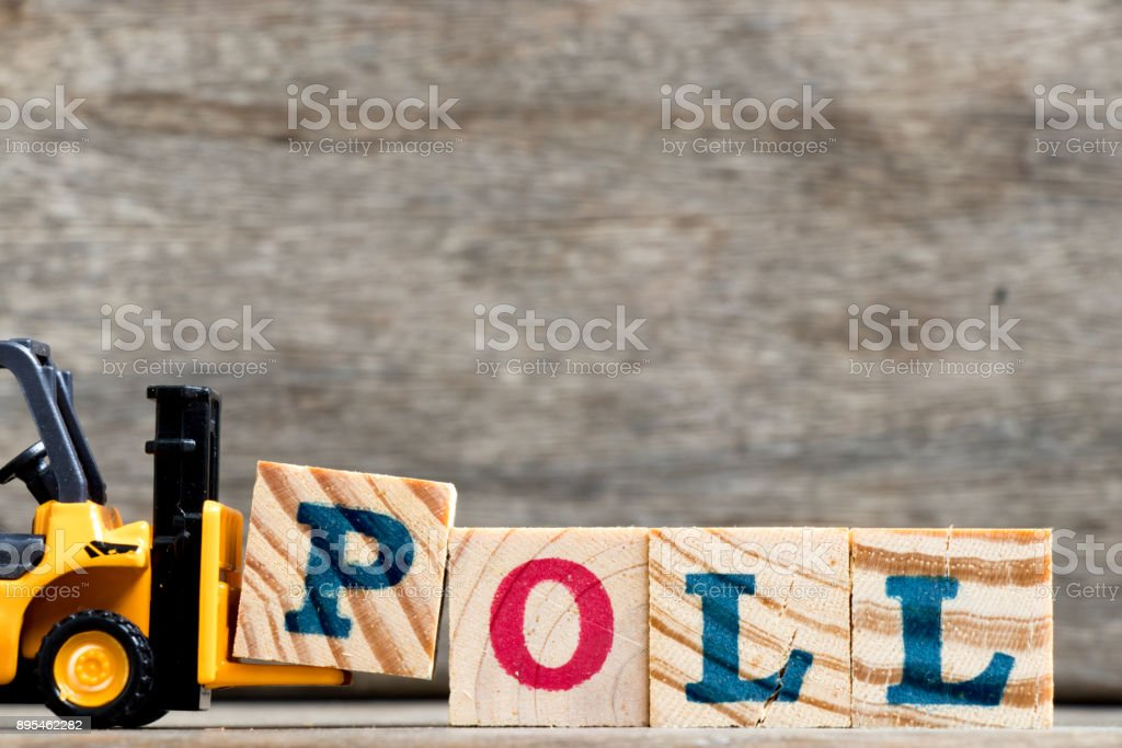 Yellow plastic forklift hold letter P to complete word poll on wood background stock photo