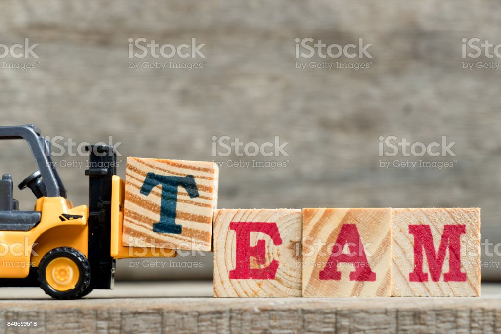 Yellow plastic forklift hold letter T to complete word TEAM on wood background stock photo