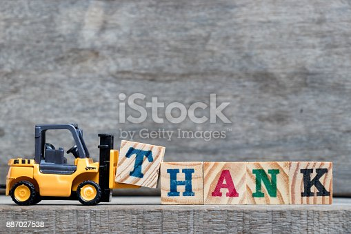 istock Yellow plastic forklift hold letter T to complete word thank on wood background 887027538