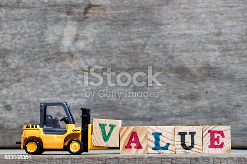 istock Yellow plastic forklift hold letter V to complete word value on wood background 883065354
