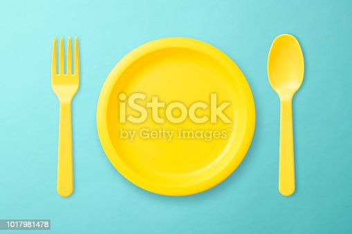 Overhead shot of yellow plastic plate, Folk, and spoon on blue background.