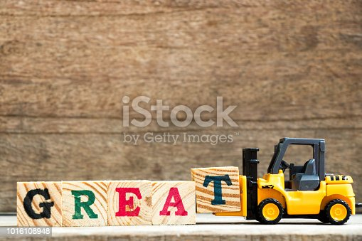 istock Yellow plastic toy forklift hold letter block T to complete word great on wood background 1016108948