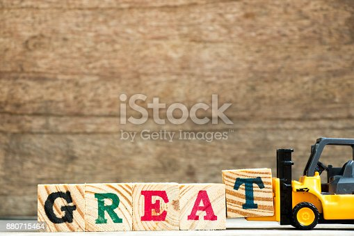 istock Yellow plastic toy forklift hold letter block T to complete word great on wood background 880715464