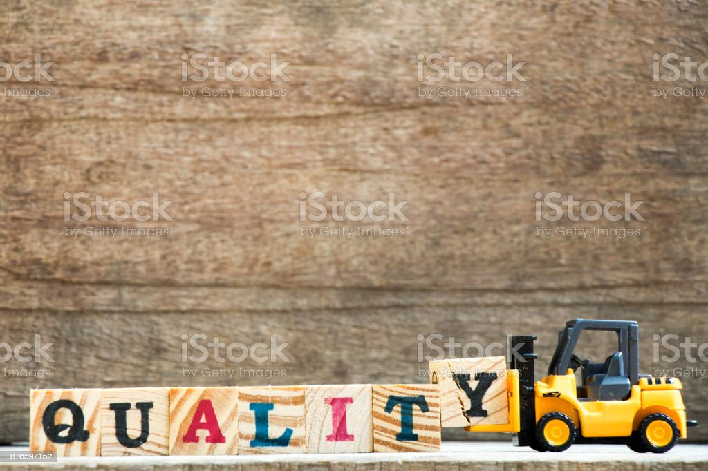 Yellow plastic toy forklift hold letter block Y to complete word quality on wood background stock photo