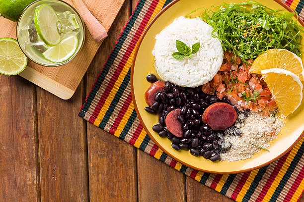 Yellow plate of feijoada with rice and margarita with lime Feijoada, the Brazilian cuisine tradition brazilian culture stock pictures, royalty-free photos & images