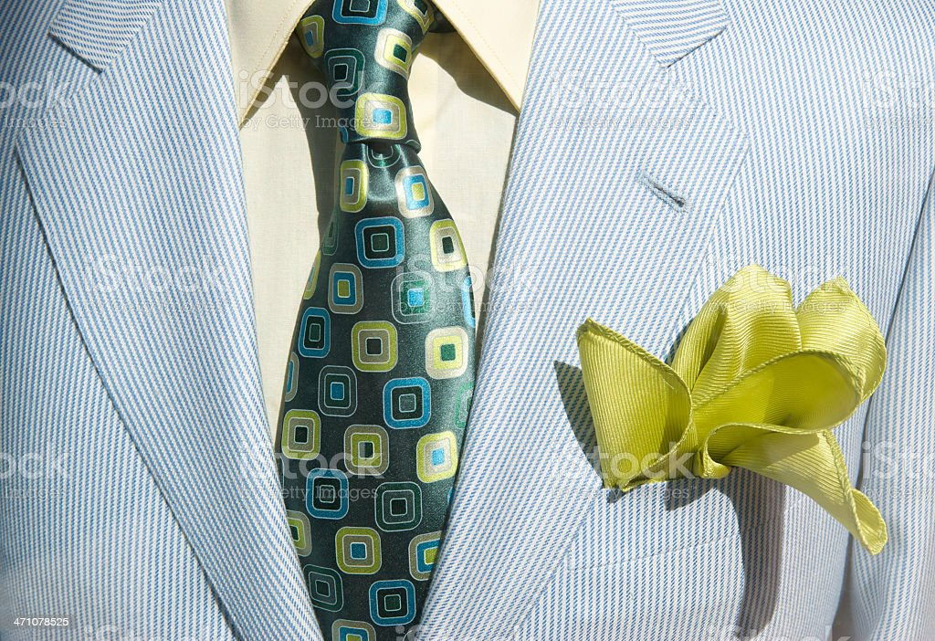 Conservative suit and bright tie are accented by a flowery chartreuse...