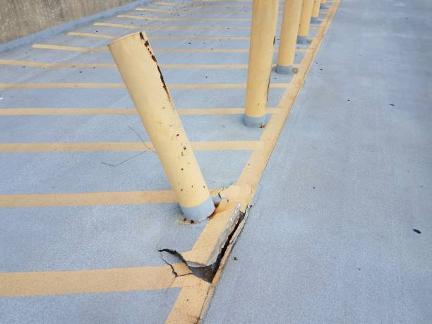yellow pole and broken grey cement after car hit it stock photo