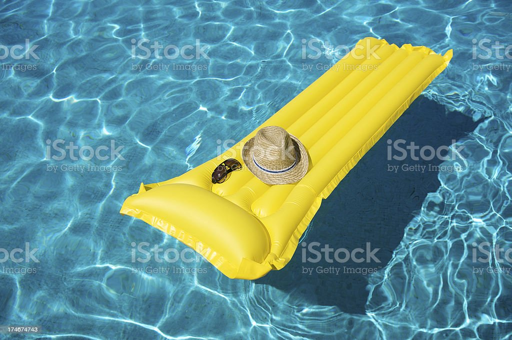 Yellow Pool Raft Floats with Hat and Sunglasses royalty-free stock photo