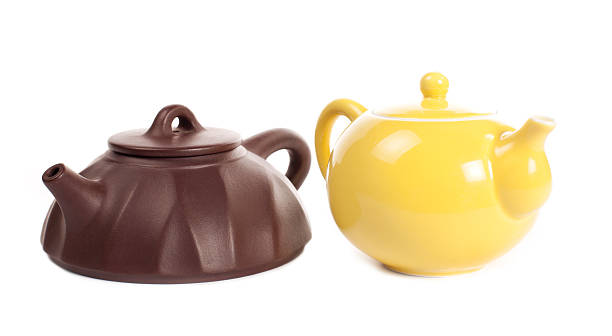 Yellow porcelain teapot and brown yixing clay one stock photo