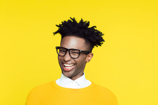 Yellow portrait of nerdy young man making funny face Funny portrait of nerdy young afro American man wearing yellow sweater laughing at the camera. cheesy grin stock pictures, royalty-free photos & images