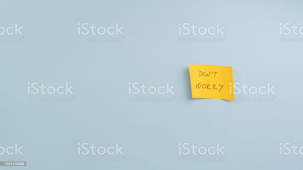 Yellow post it paper with Dont worry sign Yellow post it paper with Dont worry sign placed on blue background with plenty of copy space. Attitude Stock Photo
