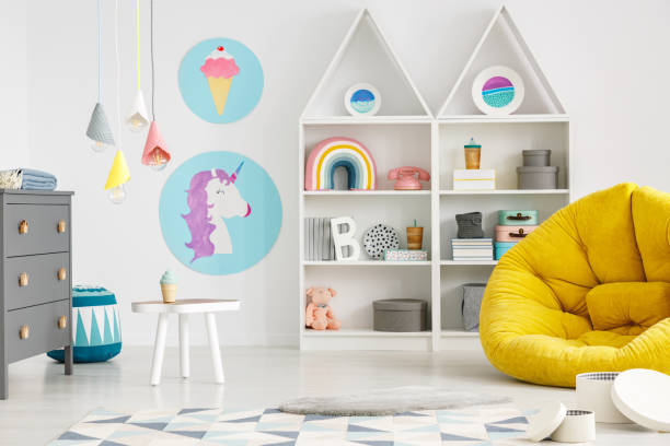 Yellow pouf in colorful child's room interior with lamps and posters stock photo