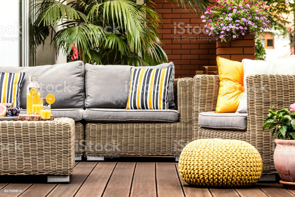 Yellow pouf on wooden terrace stock photo