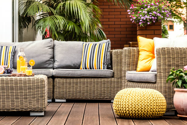 Yellow pouf on wooden terrace Yellow pouf next to rattan armchair on wooden terrace with striped pillows on sofa wicker stock pictures, royalty-free photos & images