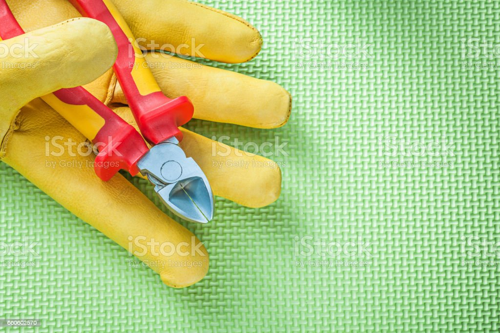 Yellow protective gloves sharp nippers on green background elect royalty-free stock photo