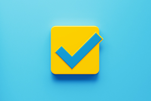 Yellow computer button with blue check mark symbol on blue background. Horizontal composition with copy space. Control concept.