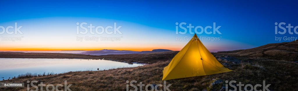 Yellow pyramid tent illuminated sunrise in idyllic mountain wilderness panorama stock photo