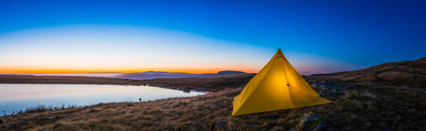 Yellow pyramid tent illuminated sunrise in idyllic mountain wilderness panorama stock photo