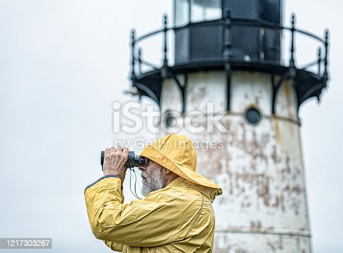 A senior adult man ancient mariner gray beard sailor sea boat captain lighthouse keeper wearing a bright yellow rubber fisherman's rain hat and matching rain slicker raincoat rain jacket is standing under his lighthouse in a light rain drizzle looking through magnifying binoculars out over the Pacific Ocean along the California coastline. Brief code #686998459 -