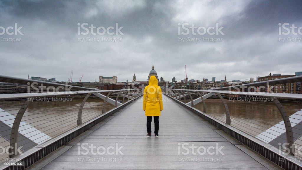 Yellow raincoat on bridge in London, UK 2 stock photo