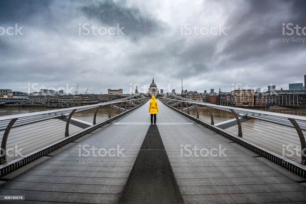 Yellow raincoat on bridge in London, UK. stock photo