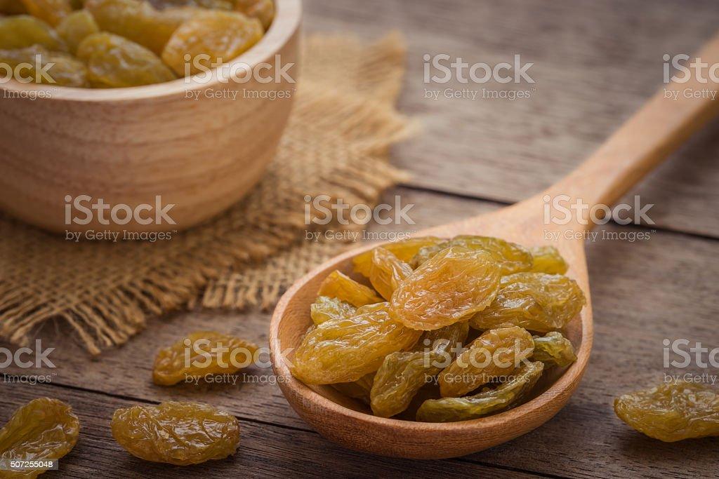Yellow raisins on wooden spoon stock photo