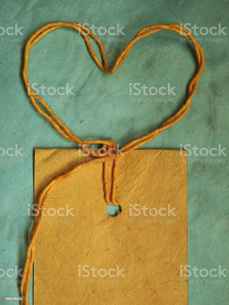 Yellow recycled paper tag on blue  textured background royalty-free stock photo