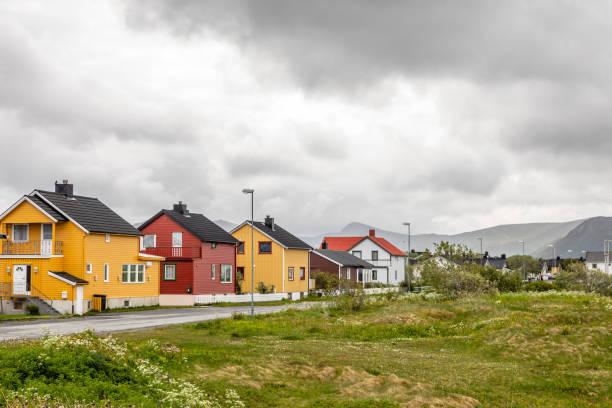 Gelbe, rote und weiße norwegische Häuser entlang der Straße in Andenes Dorf, Andoy Gemeinde, Vesteralen Bezirk, Nordland Grafschaft, Norwegen – Foto