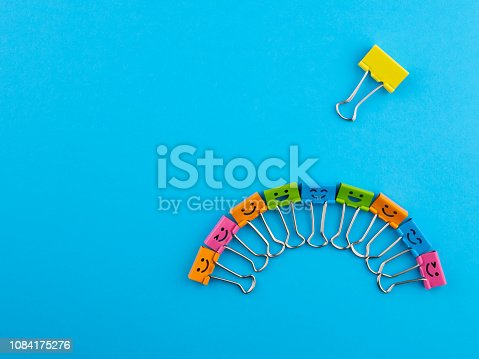 istock Yellow red green metal binder clip or multicolored paperclip on blue background with copyspace for text. Different, stand out of the crowd concept 1084175276