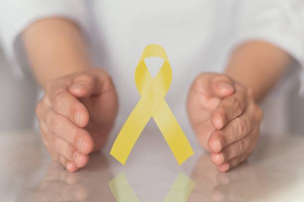 conscientização da fita amarela em mãos para câncer de bexiga, câncer ósseo / osteosarcoma, endometriose, ewings sarcoma,hidrocefalia, câncer de fígado , prevenção ao suicídio - setembro amarelo - fotografias e filmes do acervo