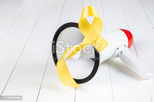 istock Yellow ribbon symbolic color for Sarcoma Bone cancer awareness and suicide prevention 1129352995