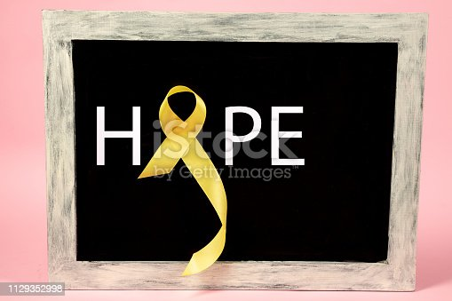 istock Yellow ribbon symbolic color for Sarcoma Bone cancer awareness and suicide prevention 1129352998