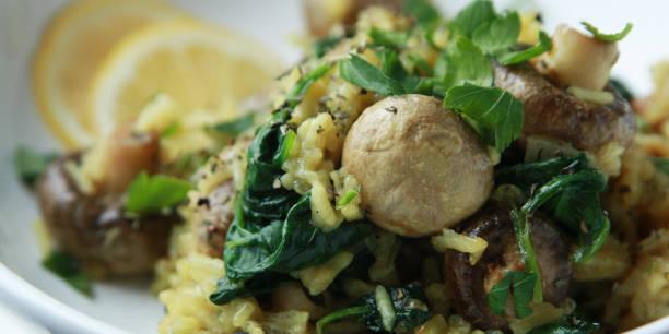 Gelber Reis mit Pilzen und Spinat. Veganes Gericht – Foto