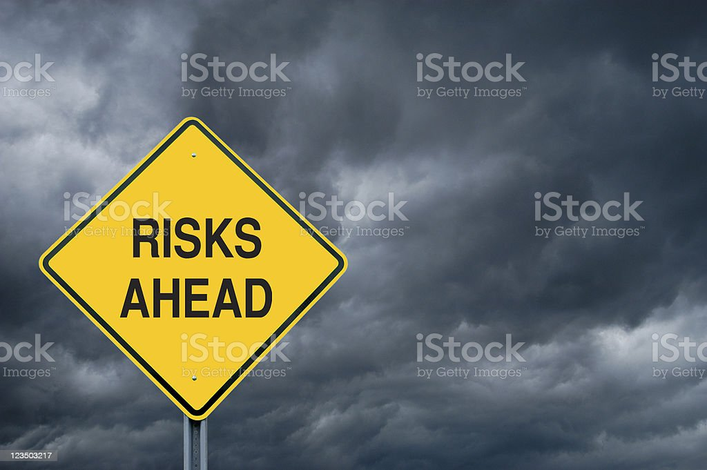 Yellow risks ahead caution sign in front of storm clouds royalty-free stock photo
