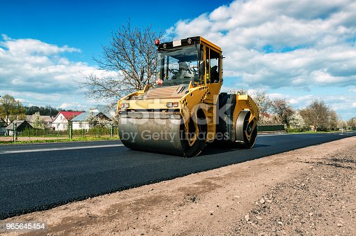 yellow road roller makes new road