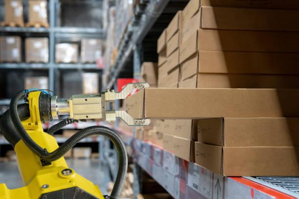 brazo robótico amarillo llevar caja de cartón en el almacén - robot fotografías e imágenes de stock