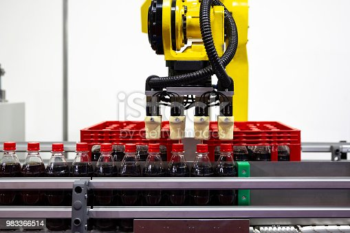 Yellow robotic arm arranges plastic soda bottles in а packing case. Automatic industrial machinery equipment.