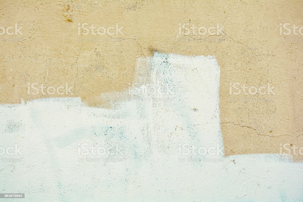 Yellow rough concrete wall with cracks and white paint royalty-free stock photo