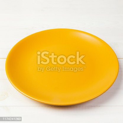 Yellow Round Plate on wooden table background. Top view, template for your design.