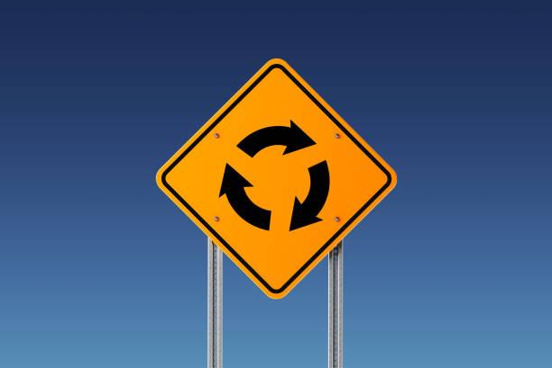 gelbe kreisverkehr zeichen auf blauem himmel - sich im kreis drehen stock-fotos und bilder