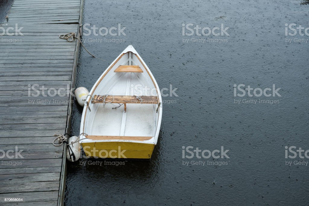 A yellow rowboat sits on an empty dock during a rain storm stock photo