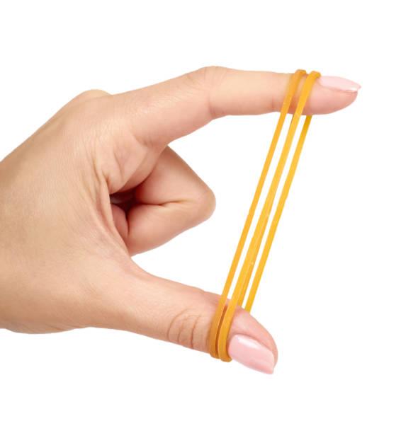 Gele elastiekjes close-up met hand geïsoleerd op een witte achtergrond. foto