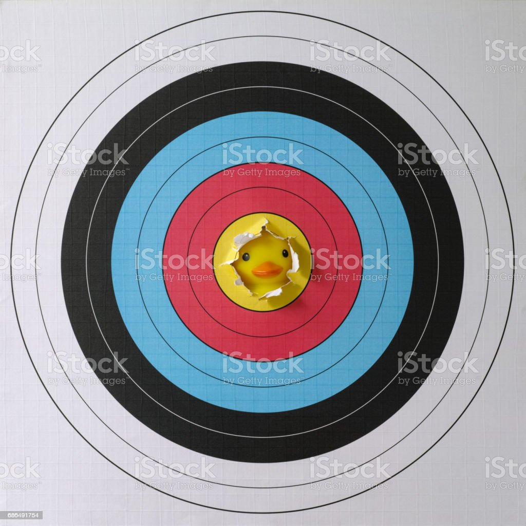 Yellow rubber duck looking from behind through a ripped part of the yellow bull's eye part of a  target. stock photo