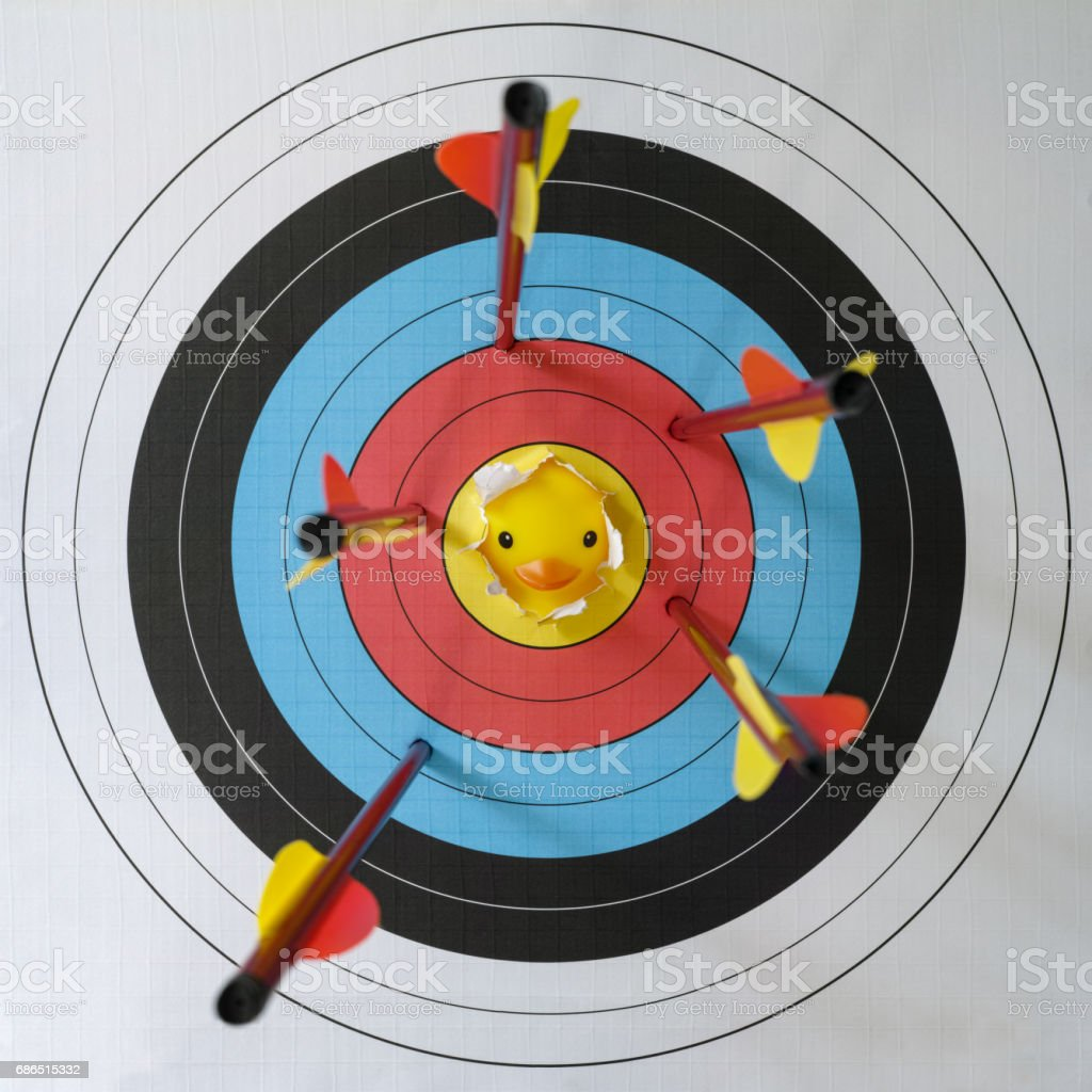 Yellow rubber duck looking from behind through a ripped part of the yellow bull's eye part of a  target with five shot arrows just missing the centre. stock photo