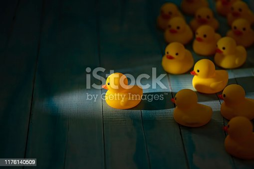 1068588904 istock photo Yellow rubber ducks in a group following one leader duck heading towards a shaft of light shining through the darkness, scene set on an old blue and white weathered wooden panel background, conceptually representing water. 1176140509