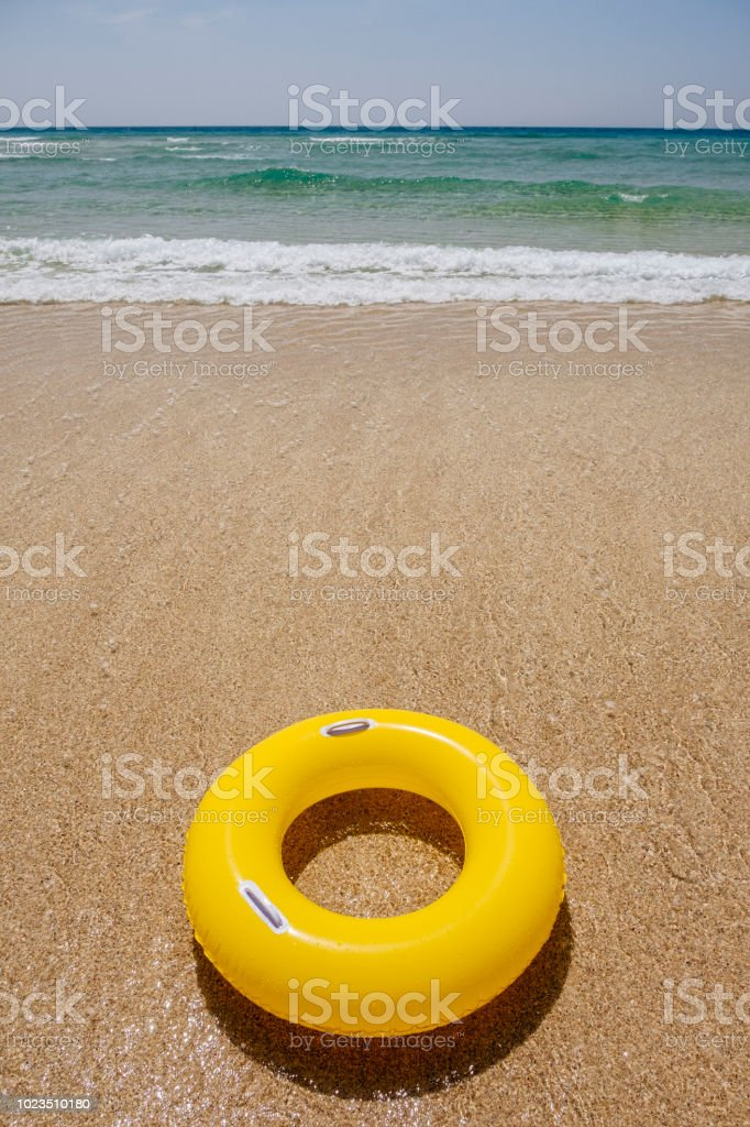 Yellow Rubber ring at Pedn Vounder Beach, Porthcurno, Cornwall on a sunny June day. stock photo
