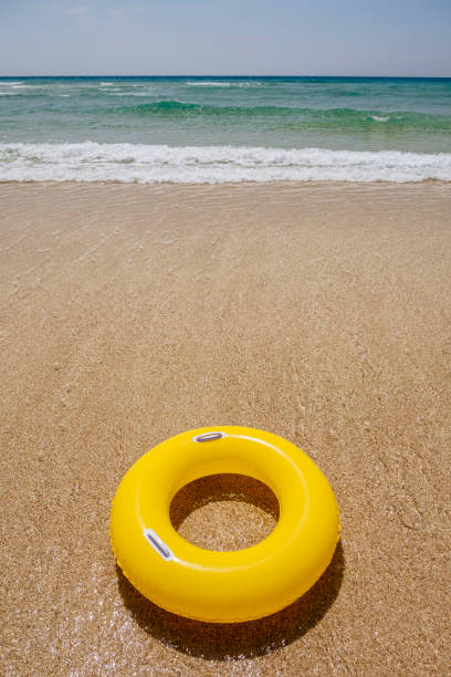 yellow rubber ring at pedn vounder beach, porthcurno, cornwall on a sunny june day. - rubber ring stock pictures, royalty-free photos & images