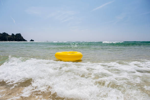yellow rubber ring at pedn vounder beach, porthcurno, cornwall on a sunny june day. - rubber ring stock photos and pictures